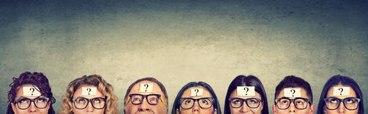 Multiethnic group of thinking people in glasses with question mark looking up. Multiethnic group of thinking people in glasses with question mark stock photo