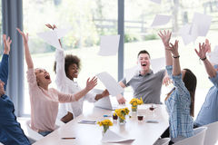 Multiethnic startup Group of young business people throwing docu. Multiethnic Group of young business people throwing documents and looking happy while Stock Images