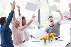 Multiethnic startup Group of young business people throwing docu. Multiethnic Group of young business people throwing documents and looking happy while Royalty Free Stock Photo