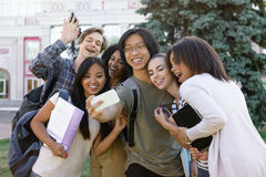 Multiethnic group of young happy students make selfie outdoors stock photos