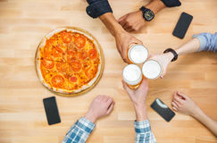 Multiethnic group of young people drinking beer and eating pizza Stock Images