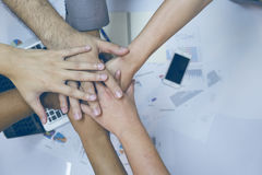 Multiethnic group of young people putting their hands on top of each other. Royalty Free Stock Photos