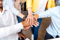 Multiethnic group of young people standing and joining hands Royalty Free Stock Photos