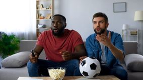Multiethnic guys watching football match, frustrated by defeat of favourite team. Stock photo royalty free stock images