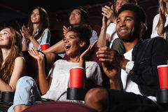 Multiethnic happy audience clapping hands. While sitting at the cinema and watching movie royalty free stock image