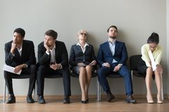Multiethnic job candidates tired of waiting in queue for intervi. Multiethnic job candidates in queue tired of long waiting in office corridor, diverse work royalty free stock photo
