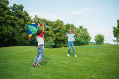 Multiethnic kids playing with kite on green lawn in park stock photos
