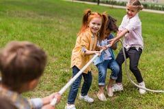 Multiethnic kids pulling rope. Happy beautiful multiethnic kids pulling rope in park Stock Image