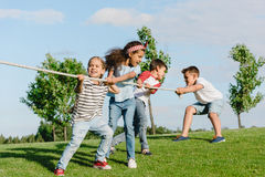Multiethnic kids pulling rope and playing tug of war in park. Cheerful multiethnic kids pulling rope and playing tug of war in park Royalty Free Stock Images