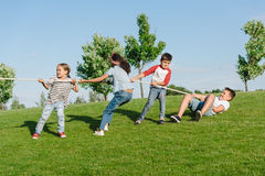 Multiethnic kids pulling rope and playing tug of war in park. Cheerful multiethnic kids pulling rope and playing tug of war in park Royalty Free Stock Photography
