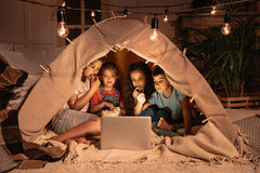 Multiethnic kids sitting tent and watching film together on laptop stock images