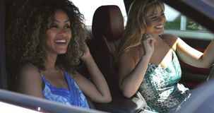 Cheerful women driving car and having fun