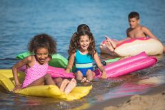 multiethnic little children swimming on colorful inflatable mattresses stock images
