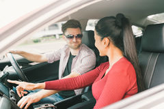 Multiethnic lover couple traveling together by car, using radio screen or GPS navigation system. Love or transportation technology stock photo