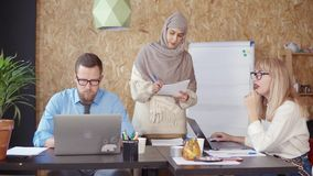 Arabian and caucasian man and women are working and talking in office. Multiethnic male and female workers are communicating in co-working area. Arabian woman is stock video
