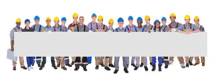 Multiethnic manual workers holding blank banner. Portrait of multiethnic manual workers holding blank banner against white background Royalty Free Stock Photo