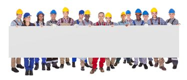 Multiethnic manual workers holding blank banner. Portrait of multiethnic manual workers holding blank banner against white background Stock Photo