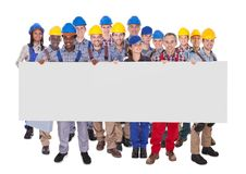 Multiethnic manual workers holding blank banner Stock Photos
