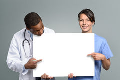 Multiethnic medical team holding a white sign. Multiethnic medical team of an African doctor in a lab coat and stethoscope and a nurse in scrubs holding a blank Royalty Free Stock Images