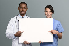 Multiethnic medical team holding a white sign Royalty Free Stock Images