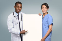 Multiethnic medical team holding a white sign Royalty Free Stock Photos