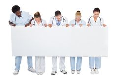 Multiethnic medical team looking at blank billboard Stock Photo