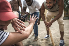 Multiethnic men attacking other one with baseball bats Royalty Free Stock Photo