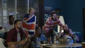 Diverse fans watching game. Multiethnic men and woman sport fans with British flag watching TV and having fail and unhappy with result stock video