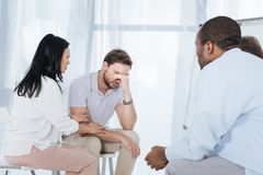 Multiethnic mid adult people supporting depressed man. Multiethnic mid adult people supporting depressed men during anonymous group therapy Royalty Free Stock Image