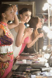 Multiethnic Models Applying Makeup In Dressing Room Mirror Stock Images