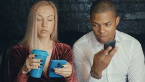 Multi-ethnic multiracial busy couple using smarkphone at cafe or coffee shop. stock footage