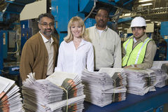Multiethnic Operators With Stack Of Newspapers In Factory Royalty Free Stock Photography
