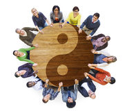 Multiethnic People Holding Hands with Yin Yang Symbol Stock Photo