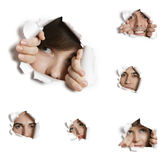Multiethnic people looking through ripped paper holes Royalty Free Stock Images