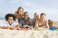Multiethnic People Lying On Sand Stock Photo