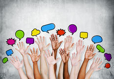 Multiethnic People's Hands Raised with Speech Bubbles Royalty Free Stock Images