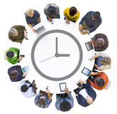 Multiethnic People Using Digital Devices with Clock Symbol Stock Photos