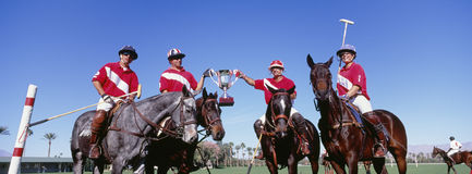 Multiethnic polo team celebrating with trophy on field stock photo