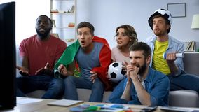 Multiethnic Portugal friends watching football match at home, supporting team royalty free stock image