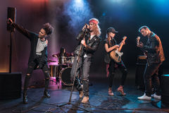 Multiethnic rock and roll band performing music on stage Royalty Free Stock Image