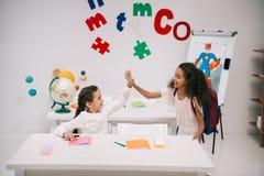 Multiethnic schoolgirls giving high five in classroom Royalty Free Stock Image