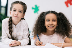 Multiethnic schoolgirls smiling at camera while studying together in classroom Stock Photos