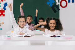 Multiethnic schoolkids showing thumbs up while sitting at desks in classroom Stock Image