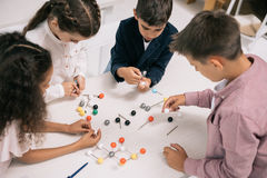 Multiethnic schoolkids studying with molecular model at chemistry lesson. Concentrated multiethnic schoolkids studying with molecular model at chemistry lesson Stock Photography