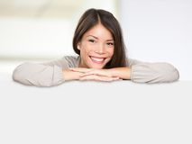 Multiethnic sign woman happy. Asian sign woman happy showing blank empty billboard sign leaning causual and relaxed smiling content. Multiethnic woman model of Royalty Free Stock Photos