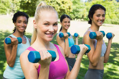 Multiethnic sporty women weightlifting Stock Photos