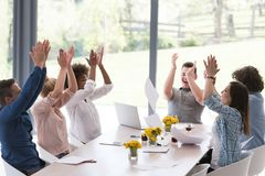 Multiethnic startup Group of young business people throwing docu. Multiethnic Group of young business people throwing documents and looking happy while Royalty Free Stock Images