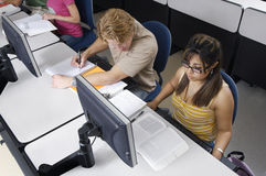 Multiethnic Students In Computer Lab. High angle view of multiethnic students studying together in computer lab Royalty Free Stock Photo