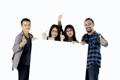 Multiethnic students with empty banner. Group of multiethnic college students showing thumbs up while holding an empty banner, isolated on white background Royalty Free Stock Photo