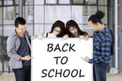 Multiethnic students show text of Back to School Royalty Free Stock Images